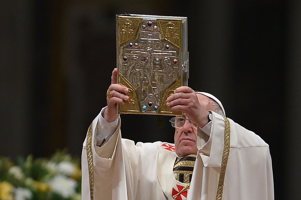. Pope Francis lifts up the book of Gospels during the Easter Vigil at the St Peter basilica in Vatican. Easter Vigil, also called the Paschal Vigil is a service held in traditional Christian churches as the first official celebration of the Resurrection of Jesus.  AFP PHOTO / FILIPPO MONTEFORTE/AFP/Getty Images