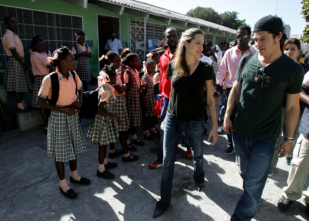 . As Haitian schoolchildren look on, actress Angelina Jolie, center, and actor Brad Pitt, right, tour the Immaculate Conception School, in Port au Prince, Haiti, Friday, Jan. 13, 2006. Many of the kids at the school receive scholarships to study with support from Yele Haiti, a charity founded by Haitian-born hip-hop musician Wyclef Jean, who walks behind Jolie at left, and who hosted Pitt and Jolie\'s visit to Haiti. (AP Photo/Brennan Linsley)