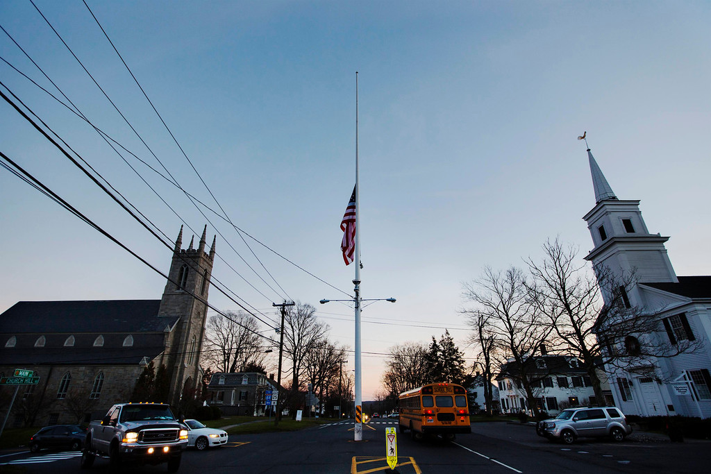 . A U.S. flag flies at half staff as a school bus drives past in the town of Newtown, Connecticut after a shooting nearby at Sandy Hook Elementary School, December 14, 2012. A heavily armed gunman opened fire inside a Connecticut elementary school on Friday, killing 26 people, including 20 children, in the latest in a series of shooting rampages across the United States this year, U.S. media reported. REUTERS/Lucas Jackson
