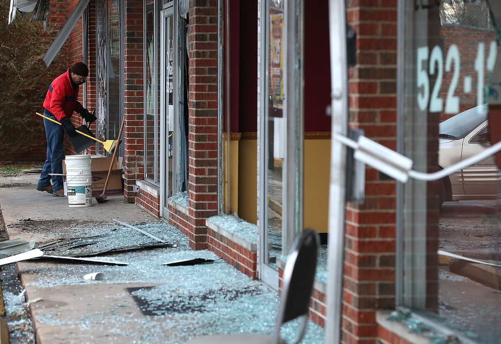 . A worker cleans up glass at a building that was damaged during a demonstration on November 25, 2014 in Dellwood, Missouri. Demonstrators caused extensive damage in Ferguson and surrounding areas last night after a St. Louis County grand jury decided to not indict Ferguson police Officer Darren Wilson in the shooting of Michael Brown.  (Photo by Justin Sullivan/Getty Images)