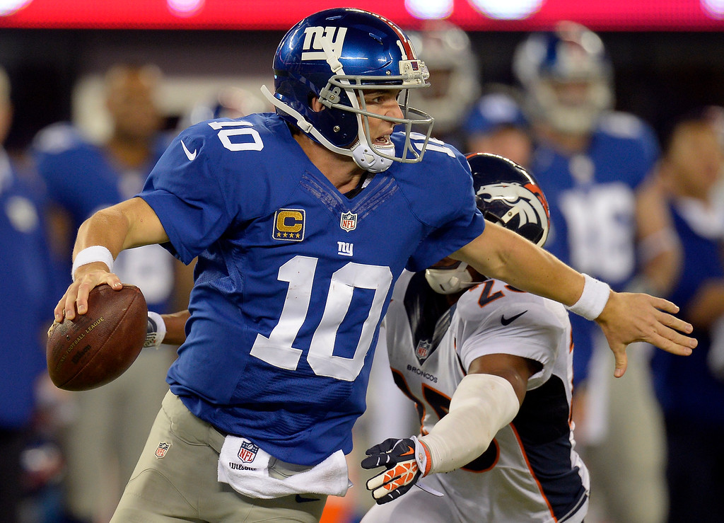 . New York Giants quarterback Eli Manning (10) escapes a sack by Denver Broncos cornerback Chris Harris (25) during the fourth quarter September 15, 2013 MetLife Stadium. (Photo by John Leyba/The Denver Post)