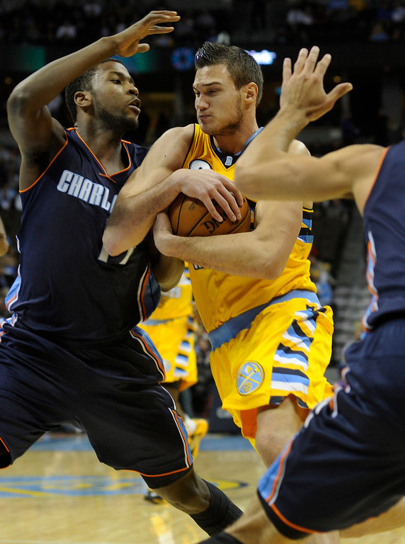 . Denver forward Danilo Gallinari (8) carried the ball like a Broncos running back as he headed to the basket in the first quarter. The Denver Nuggets hosted the Charlotte Bobcats at the Pepsi Center Saturday night, December 22, 2012.  Karl Gehring/The Denver Post