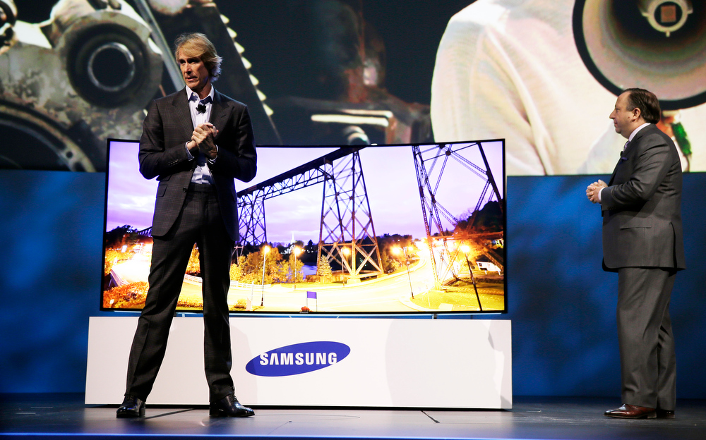 . Director Michael Bay, left, and Samsung Electronics America Executive Vice President Joe Stinziano introduce a 105-inch ultra high definition curved television during a news conference at the International Consumer Electronics Show, Monday, Jan. 6, 2014, in Las Vegas. (AP Photo/Isaac Brekken)