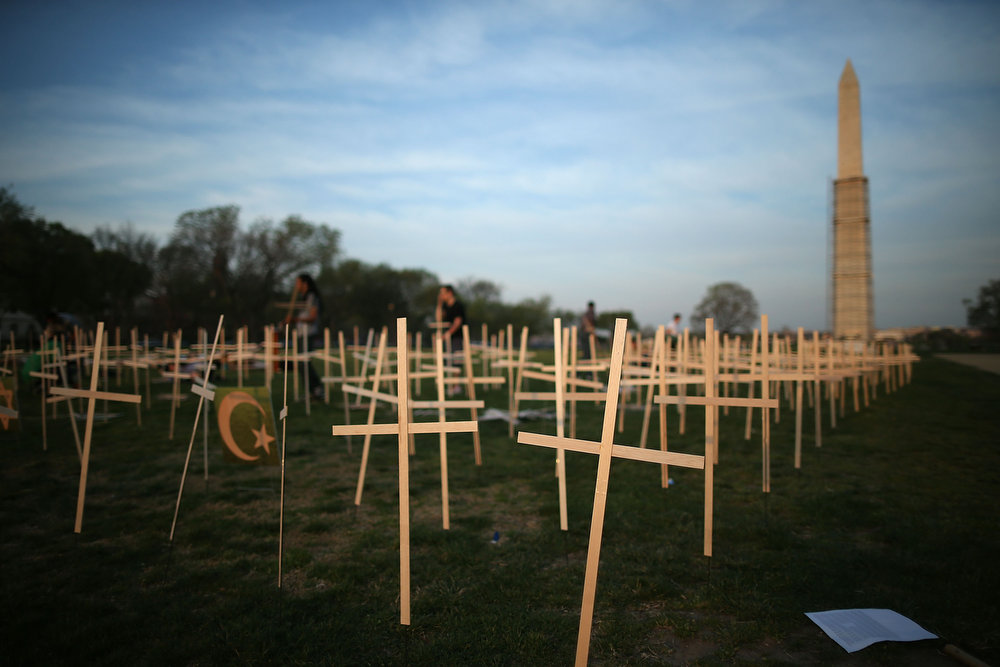 . Volunteers place grave markers on the National Mall as over 3,300 crosses, stars of David, and other religious symbols are placed to remember those affected by gun violence on April 11, 2013 in Washington, DC. Clergy from Newtown, Connecticut, and others will begin a 24- hour vigil to urge Congress into passing tougher gun laws. (Photo by Mark Wilson/Getty Images)