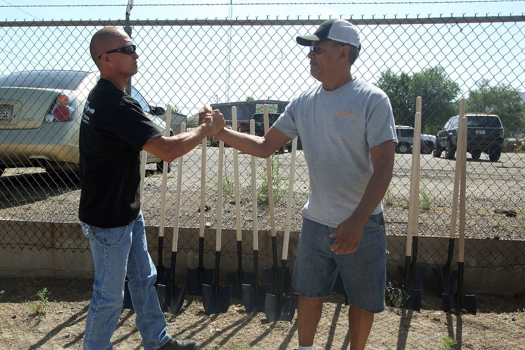 . Former firefighter David Bowden(L)and Anthony Delgrolice shake hands after placing 19 shovels in the dirt  as a memorial outside of Granite Mountain Hotshots Fire Station 7 in Prescott, Arizona July 2, 2013. AFP PHOTO / KRISTA Kennell/AFP/Getty Images
