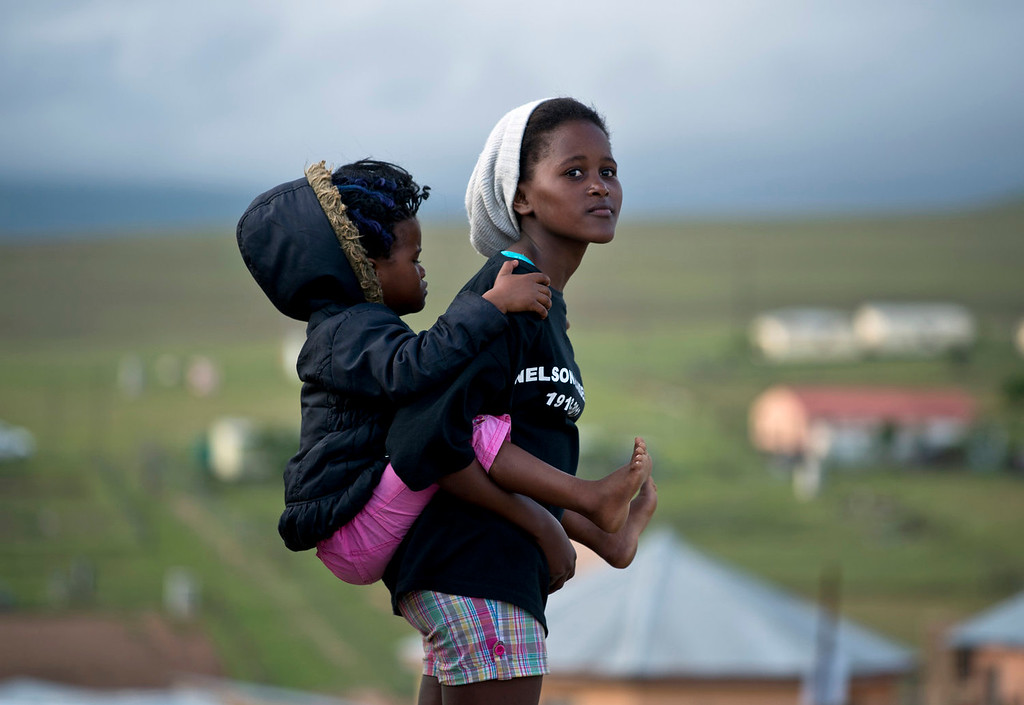 . A young woman carrying a baby looks towards Nelson Mandela\'s family house in Qunu where the coffin of South African former president arrived on December 14, 2013 before his funeral tomorrow. Mandela, the revered icon of the anti-apartheid struggle in South Africa and one of the towering political figures of the 20th century, died in Johannesburg on December 5 at age 95.  AFP PHOTO / PEDRO UGARTEPEDRO UGARTE/AFP/Getty Images