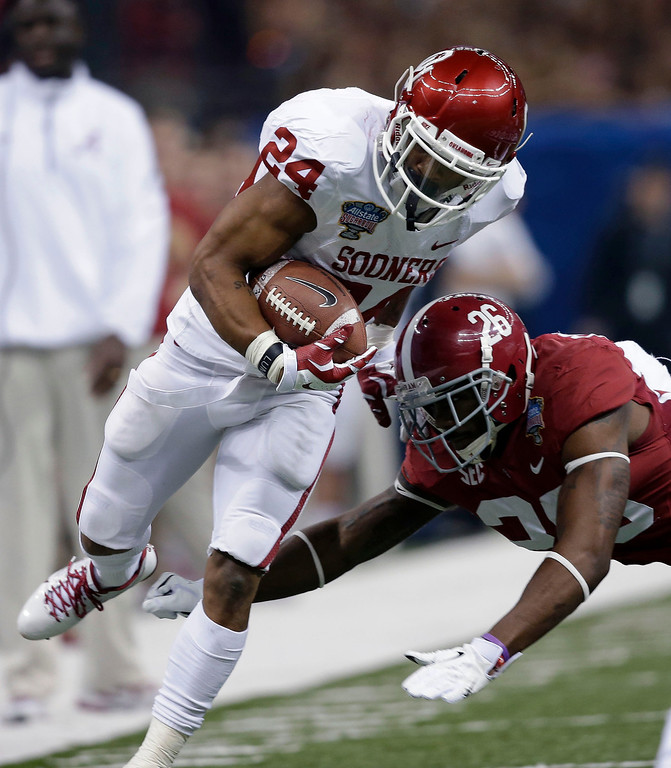 . Alabama defensive back Landon Collins (26) tries to tackle Oklahoma running back Brennan Clay (24) during the first half of the Sugar Bowl NCAA college football game, Thursday, Jan. 2, 2014, in New Orleans. (AP Photo/Patrick Semansky)
