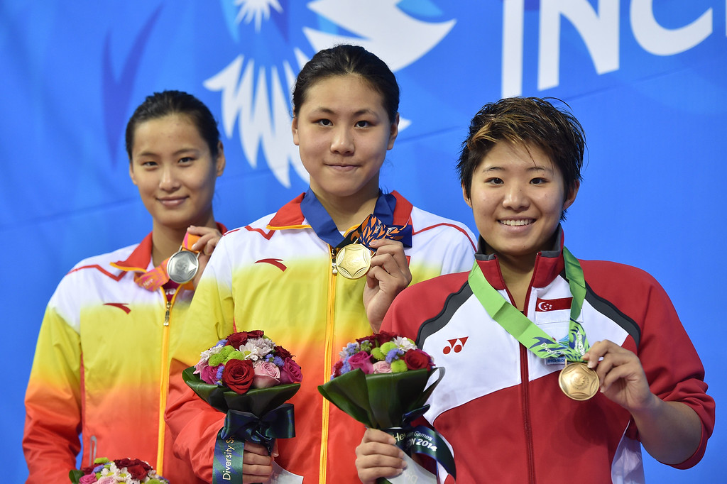 . (L-R) Silver medallist  China\'s Lu Ying , gold medallist China\'s Chen Xinyi and bronze medallist Singapore\'s Tao Li pose with their medals on the podium during the victory ceremony for the women\'s 100m butterfly swimming event during the 17th Asian Games at the Munhak Park Tae-hwan Aquatics Centre in Incheon on September 23, 2014.   PHILIPPE LOPEZ/AFP/Getty Images
