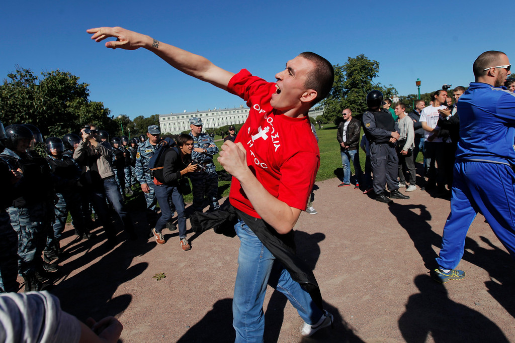 """. An anti-gay demonstrator throws coins at activists protesting law on gay \""""propaganda\"""" in St.Petersburg, Russia, Friday, Sept. 6, 2013. About two dozen activists have rallied in St. Petersburg to protest a new Russian law banning gay \""""propaganda\"""" and attract attention of the leaders of the world\'s 20 leading economies. The rally went on peacefully under the close watch of several hundred riot police, who separated the protesters from a few dozen anti-gay demonstrators. (AP Photo/Elena Ignatyeva)"""