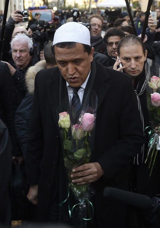 . Imam of the Mosque in Drancy and president of the French association of Imam\'s Hassen Chalghoumi (In white skull-cap) arrives to lay a floral tribute and to pay his respects outside the offices of the French satirical magazine Charlie Hebdo in Paris on January 8, 2015, a day after Islamist gunmen stormed the offices of the magazine, killing eight journalists, two police and two others. French security forces were frantically hunting two brothers suspected of gunning down 12 people in an Islamist attack on a satirical weekly, as a stunned and outraged France fell silent to mourn the victims. AFP PHOTO / MARTIN BUREAU/AFP/Getty Images