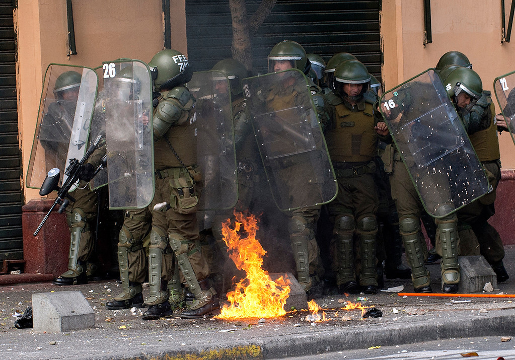 . Riot policemen protect themselves during a student protest who demand Chilean President Sebastian Pinera\'s government to improve the public education quality, in Santiago, on April 11,2013. MARTIN BERNETTI/AFP/Getty Images
