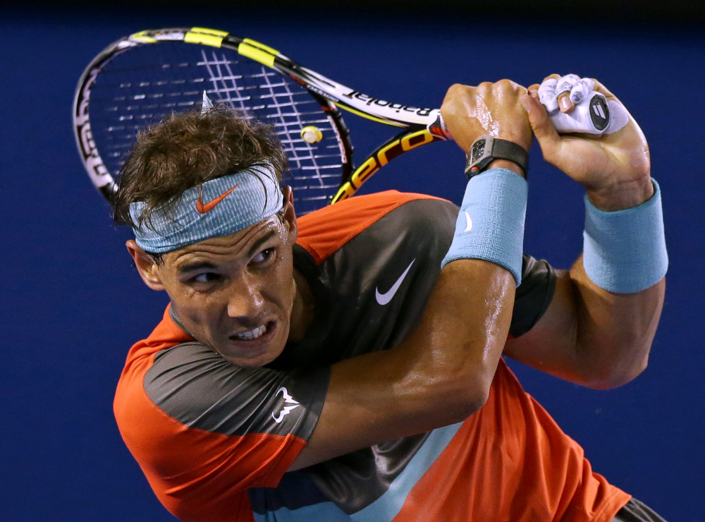 . Rafael Nadal of Spain follows through on a shot to Roger Federer of Switzerland during their semifinal at the Australian Open tennis championship in Melbourne, Australia, Friday, Jan. 24, 2014.(AP Photo/Aaron Favila)