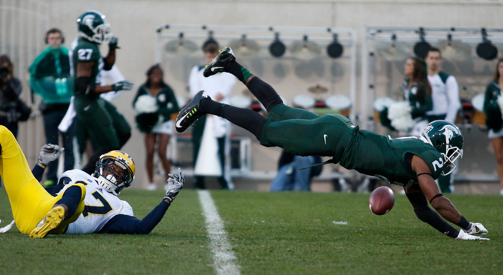 . Michigan State\'s Darian Hicks (2) breaks up a pass intended for Michigan\'s Freddy Canteen during the fourth quarter of an NCAA college football game, Saturday, Oct. 25, 2014, in East Lansing, Mich. Michigan State won 35-11. (AP Photo/Al Goldis)