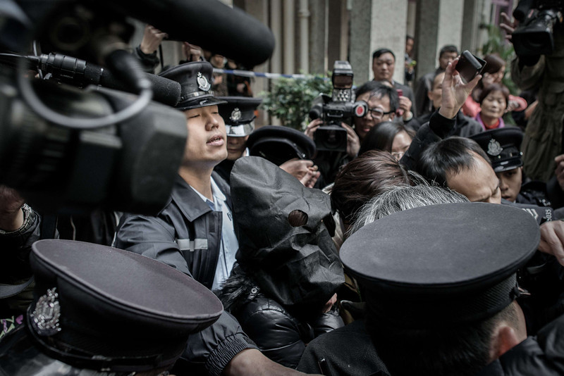 . Police officers escort the woman (C-wearing a black mask) who allegedly tortured Indonesian maid Erwiana Sulistyaningsih as they walk out of her residence in Hong Kong January 21, 2014.  Hong Kong police interviewed the Indonesian maid, a day after police in Hong Kong arrested her employer accused of abusing her and a second Indonesian helper, as she attempted to board a flight to Thailand at the city\'s airport.  (PHILIPPE LOPEZ/AFP/Getty Images)