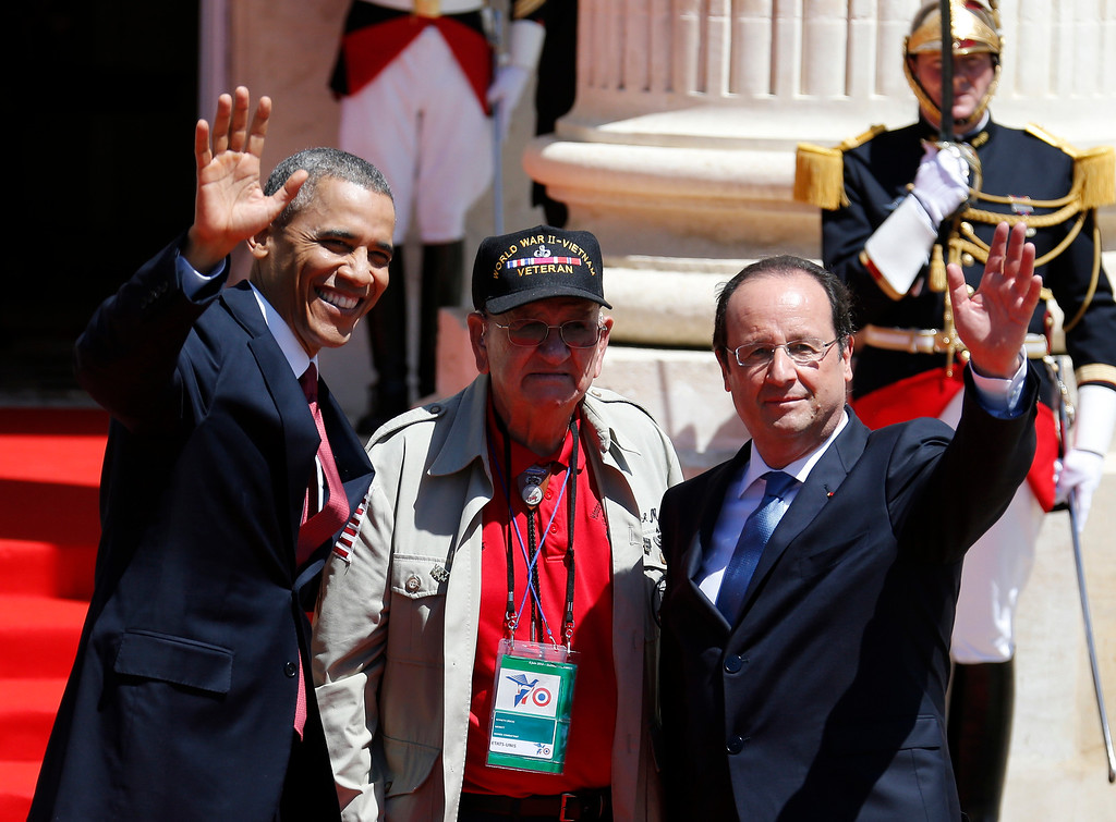". U.S. President Barack Obama, left, and French President Francois Hollande, right, waves with World War II veteran Kenneth ""Rock\"" Merritt as they arrive for the official lunch at Benouville castle, in Normandy, France, Friday, June 6, 2014. World leaders and veterans paid tribute on the 70th anniversary of the World War Two D-Day landings to soldiers who fell in the liberation of Europe from Nazi German rule, as host France sought to use the event to achieve a thaw in the Ukraine crisis. (Regis Duvignau, pool)"