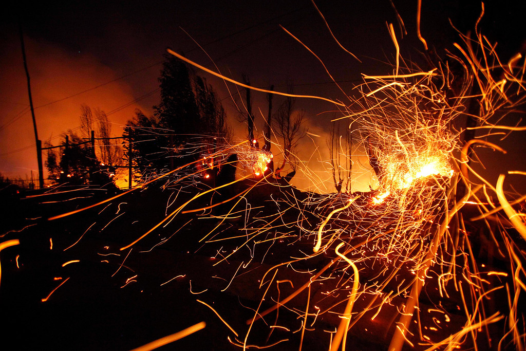 . Sparks fly carried by the wind as a large forest fire reaches urban areas in Valparaiso, Chile, Sunday April 13, 2014. Authorities say the fires have destroyed hundreds of homes, forced the evacuation of thousands and claimed the lives of at least seven people.  ( AP Photo/ Luis Hidalgo)