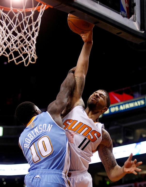 . Denver Nuggets point guard Nate Robinson (10) fouls Phoenix Suns forward Markieff Morris (11) in the third quarter of an NBA basketball game, Sunday, Jan. 19, 2014, in Phoenix. (AP Photo/Rick Scuteri)