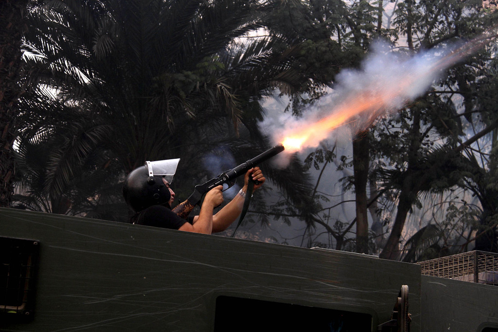 . An Egyptian riot policeman fires tear gas in Cairo, Egypt, Friday, Nov. 29, 2013, to disperse hundreds of Islamist demonstrators defying a new protest law that has drawn widespread criticism from the international community and democracy advocates.(AP Photo/Ahmed Gomaa)