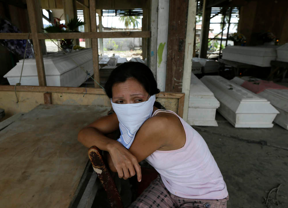 Description of . Arlene Barcelona sits at a damaged public market for the wake of her mother Felicitas who was killed at the height of Tuesday's typhoon Bopha at New Bataan township, Compostela Valley in southern Philippines Saturday Dec. 8, 2012. Search and rescue operations following a typhoon that killed nearly 600 people in the southern Philippines have been hampered in part because many residents of this ravaged farming community are too stunned to assist recovery efforts, an official said Saturday. (AP Photo/Bullit Marquez)