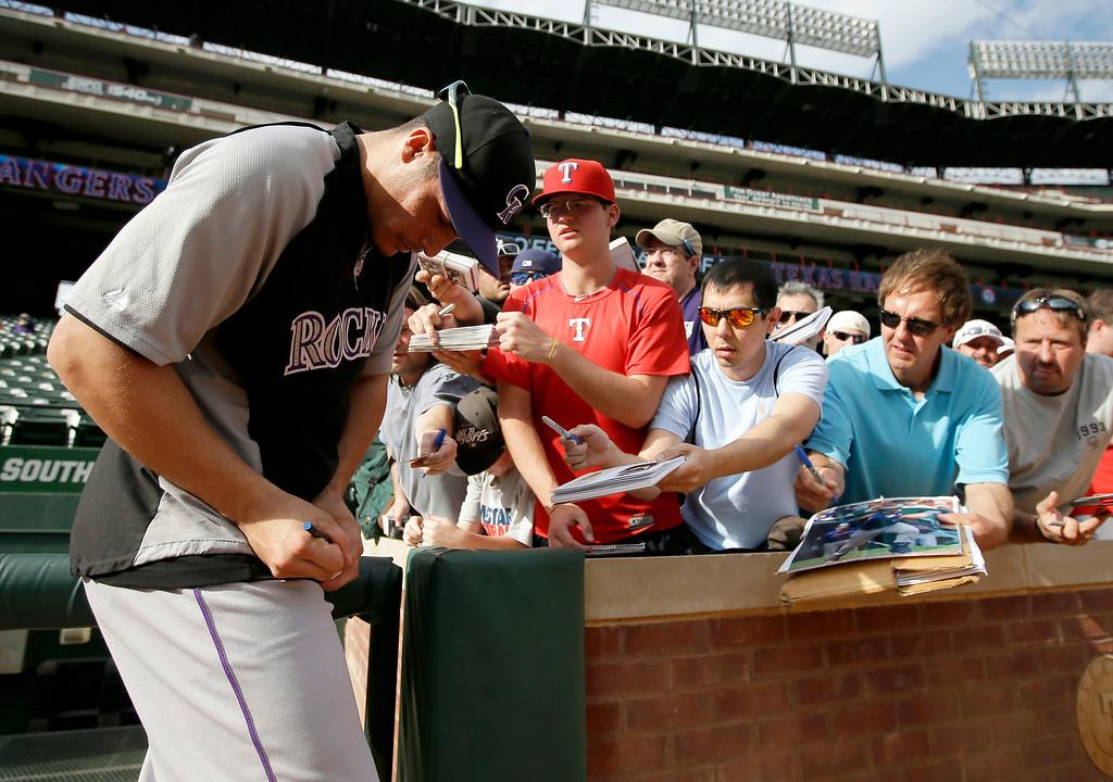 . Colorado Rockies\' Nolan Arenado signs autographs for fans during batting practice before a baseball game against the Texas Rangers, Wednesday, May 7, 2014, in Arlington, Texas. (AP Photo/Tony Gutierrez)