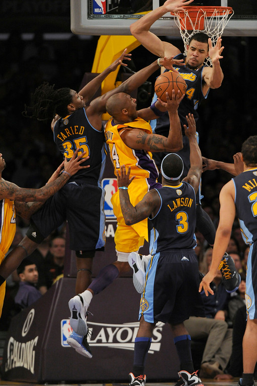 . Los Angeles Lakers shooting guard Kobe Bryant (24) gets mobbed by Denver Nuggets center JaVale McGee (34) forward Kenneth Faried (35) as he drives to the basket in game 5 of the first round of the NBA playoffs Tuesday, May 8, 2012 at Staples Center. John Leyba, The Denver Post