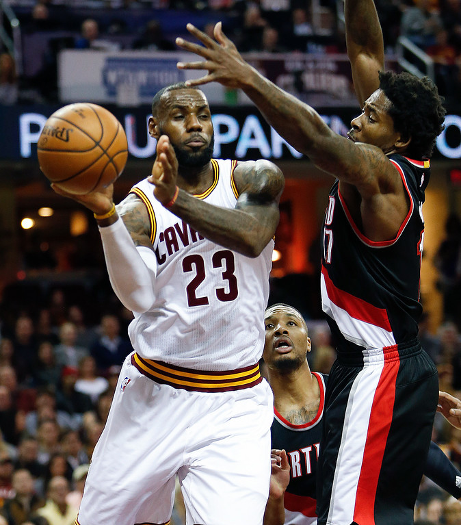 . Cleveland Cavaliers\' LeBron James (23) passes around Portland Trail Blazers\' Ed Davis (17) during the first half of an NBA basketball game Wednesday, Nov. 23, 2016, in Cleveland. The Cavaliers won 137-125. (AP Photo/Ron Schwane)