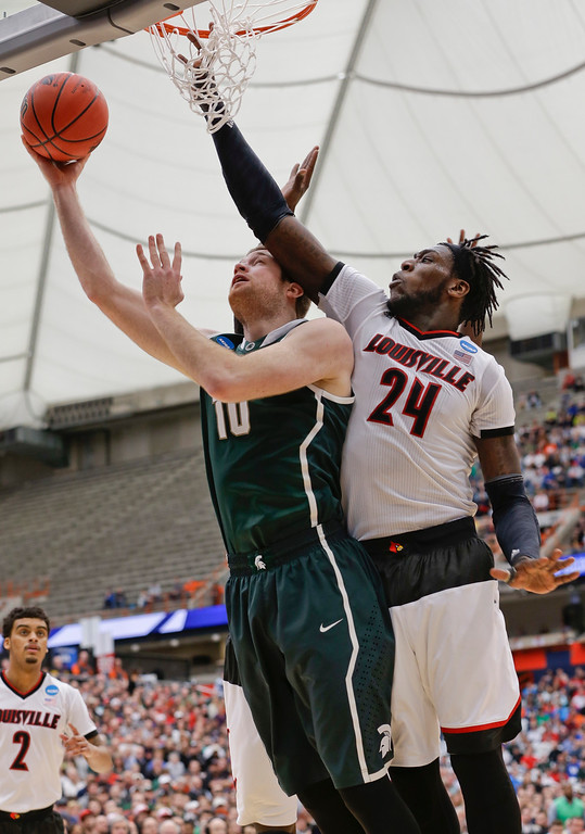 . Michigan State\'s Matt Costello (10) drives past Louisville\'s Montrezl Harrell (24) during the second half of a regional final in the NCAA men\'s college basketball tournament Sunday, March 29, 2015, in Syracuse, N.Y. (AP Photo/Seth Wenig)