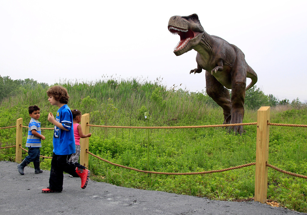 . In this Friday, May 25, 2012 file photo, children stand near a life-size Tyrannosaurus Rex dinosaur model as it moves and growls in an interactive display at Field Station Dinosaurs in Secaucus, N.J. Scientists used to think T. rex stood tall, but they abandoned that idea decades ago. Now, the ferocious dinosaur is depicted in a bird-like posture, tail in the air and head pitched forward of its two massive legs. (AP Photo/MelEvans)