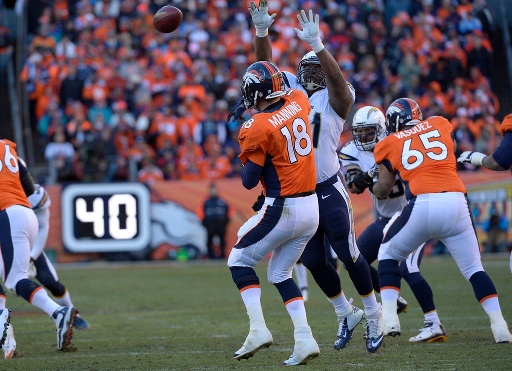 . Denver Broncos quarterback Peyton Manning (18) gets the ball away under pressure during the second quarter. The Denver Broncos vs. The San Diego Chargers in an AFC Divisional Playoff game at Sports Authority Field at Mile High in Denver on January 12, 2014. (Photo by Joe Amon/The Denver Post)