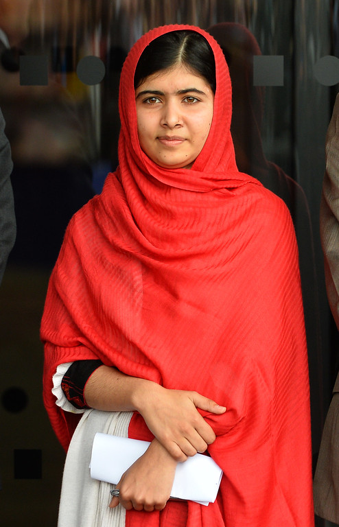 . In this photograph taken September 3, 2013 Malala Yousafzai, the 16-year-old Pakistani advocate for girls education who was shot in the head by the Taliban in 2012, stands before officially opening The Library of Birmingham in Birmingham, central England. The Nobel Peace Prize went October 10, 2014 to 17-year-old Pakistani Malala Yousafzai and India\'s Kailash Satyarthi for their work promoting children\'s rights.     AFP PHOTO / PAUL ELLIS//AFP/Getty Images