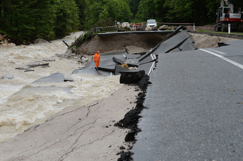 . A person looks at the  heavily damaged  road  between Lofer and Waidring in the Austrian province of Tyrol,  Monday, June. 3, 2013. Heavy rainfalls caused floods along rivers and lakes in Germany, Austria, Switzerland and the Czech Republic. (AP Photo/Kerstin Joensson)
