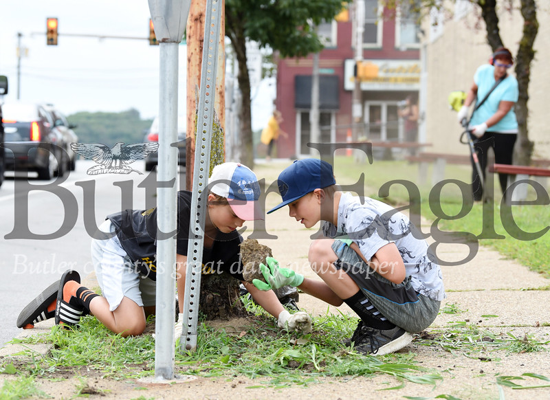 "Harold Aughton/Butler Eagle: Best friends, Kellen McFadden, 11 (left) and Conor Bradrick, 11, both of Butler discover a large rock while pulling weeds along Wayne Street, Monday, August 26 as part of the BC3's ""Hope is Dope"" initiative to change the energy and discussion around those struggling with addiction and those in recovery."