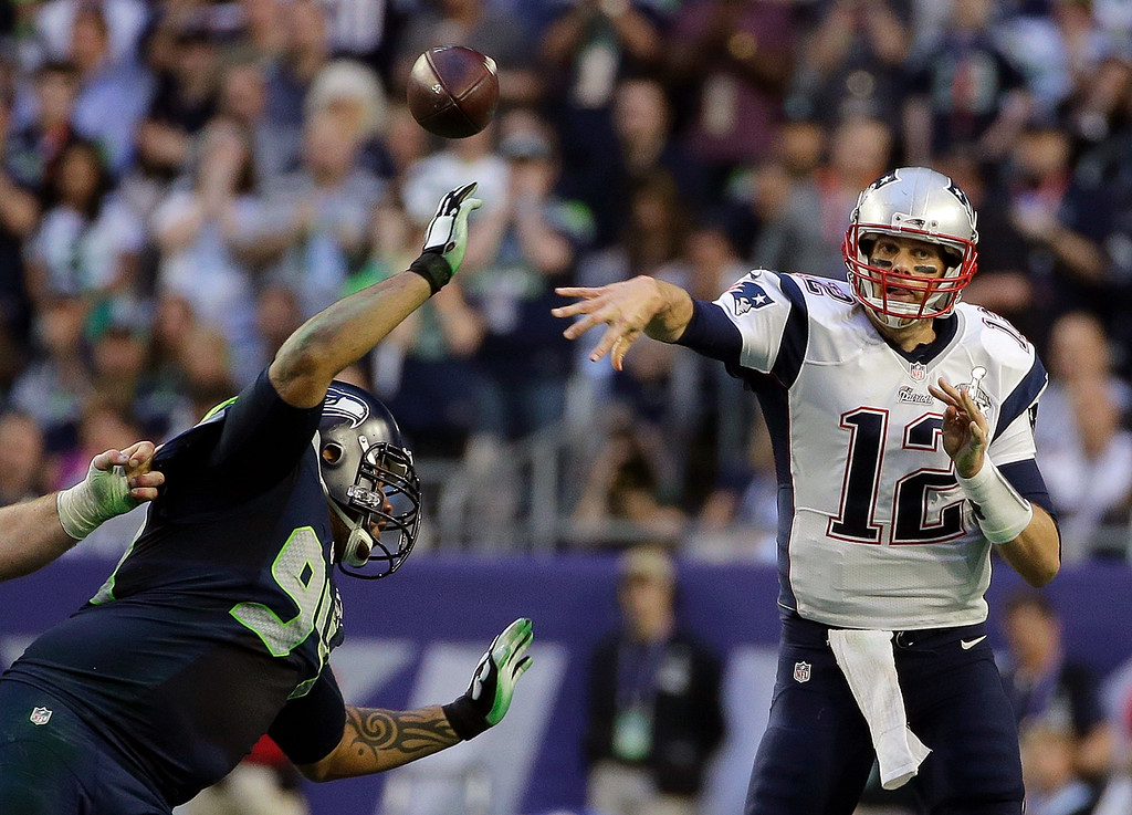 . New England Patriots quarterback Tom Brady (12) throws a pass as Seattle Seahawks defensive tackle Kevin Williams (94) pressures during the first half of NFL Super Bowl XLIX football game Sunday, Feb. 1, 2015, in Glendale, Ariz. (AP Photo/Matt Slocum)