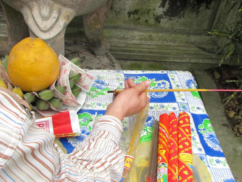 09-Offerings made here—lighting the incense. The pomelo (similar to grapefruit but larger and different in flavor) holds down the bananas which hold the money.