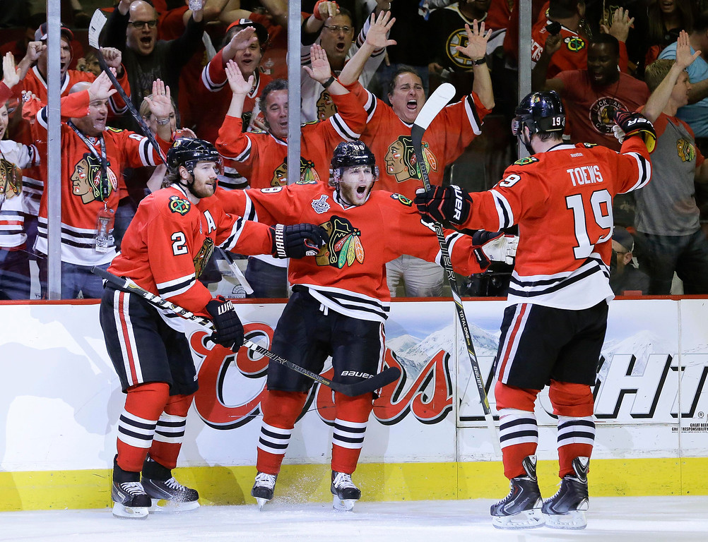 . Chicago Blackhawks defenseman Nick Leddy (8) celebrates with center Jonathan Toews (19) and defenseman Duncan Keith (2) after scoring a goal against the Boston Bruins in the second period during Game 5 of the NHL hockey Stanley Cup Finals, Saturday, June 22, 2013, in Chicago. (AP Photo/Nam Y. Huh)