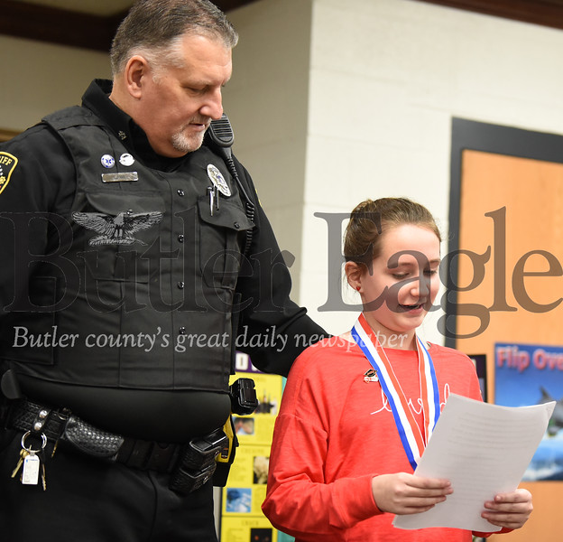 Harold Aughton/Butler Eagle: Butler County Sherriff's Deputy, Anthony Sawl, listens as 5th grader Delaney Frye reads her award-winning essay during the D.A.R.E. graduation ceremony at St. Lukes Elementary. Officer Sawl spent 10 weeks with Mrs. Garcia-Bish's  5th grade class teaching students about the dangers of drugs. The program was funded by the Butler County Human Services. Delaney took first place while siblings Connor Crotzer took second place and his sister, Olivia Crotzer on third place for their essays.
