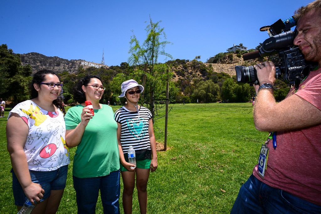 ". Yesenia Morales of Los Angeles, with her daughters Scarlett Castro and Sara Morales are interviewed by TV after Morales found a stash of ""hidden cash\"" ($80.00) at Lake Hollywood Park Sunday morning, June 1, 2014.   The Hidden cash has been turning up for the last couple of days around Los Angeles.  According to the @hiddencash twitter there will be one more drop in LA Sunday.  ( Photo by David Crane/Los Angeles Daily News )"