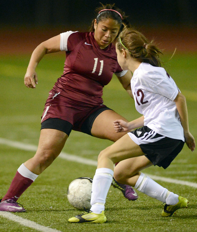 . Downey\'s Cindy Rodriguez (11) moves the ball around Torrance\'s (12) in a CIF SS Division IV quarterfinal game Thursday at Zamperini Field. Downey won the game 3-1. 20130221 Photo by Steve McCrank / Staff Photographer