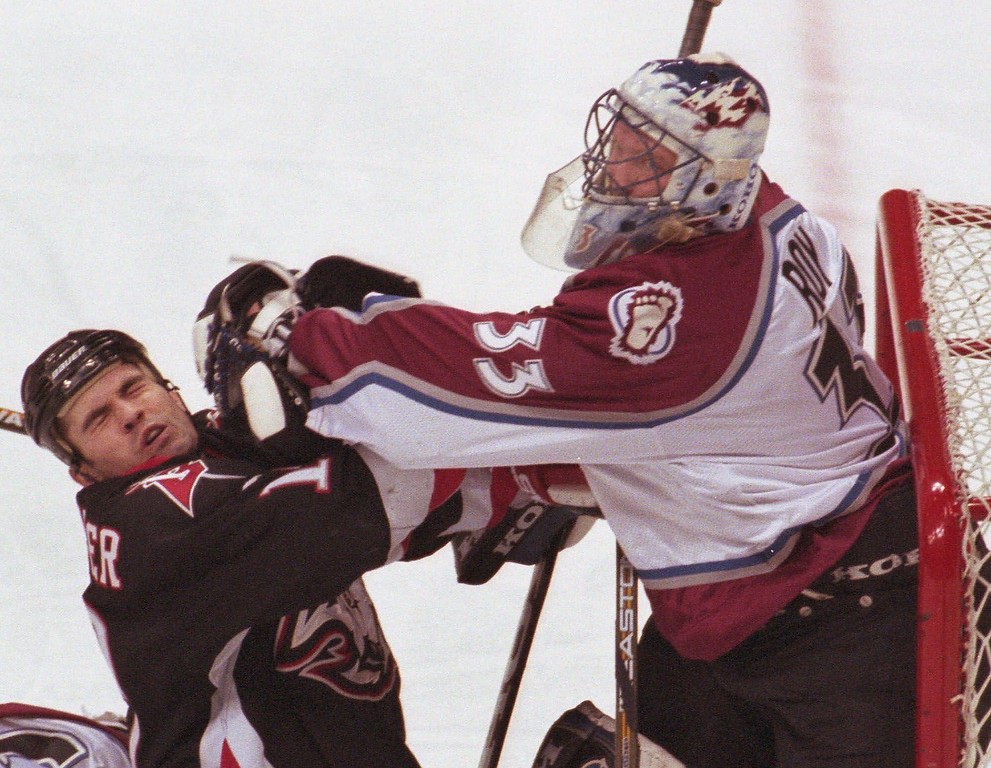 . Colorado Avalanche goalie Patrick Roy knocks back Buffalo Sabres center Brian Holzinger during the first period at the Pepsi Center in Denver Tuesday, Feb. 8, 2000. (AP Photo/Jack Dempsey)