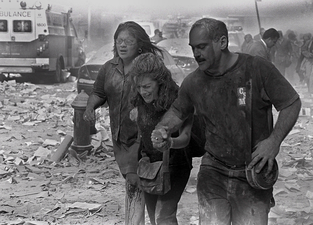 . Julie McDermott, center, walks with other victims as they make their way amid debris near the World Trade Center in New York Tuesday Sept. 11, 2001.  (AP Photo/Gulnara Samoilova)
