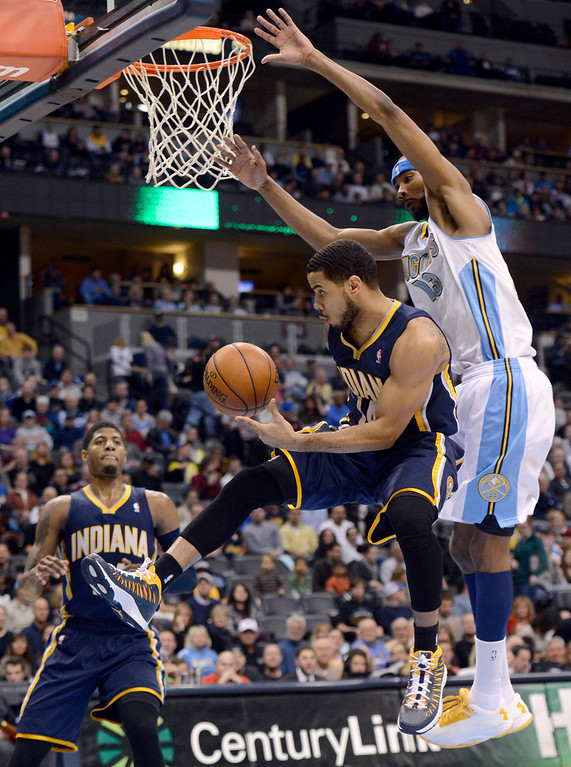 . DENVER, CO. - JANUARY 28: Indiana Pacers point guard D.J. Augustin (14) flies under the outstretched arms of Denver Nuggets small forward Corey Brewer (13) as he passes to Indiana Pacers small forward Paul George (24)  during the second quarter January 28, 2013 at Pepsi Center. The Denver Nuggets host the Indiana Pacers in NBA action. (Photo By John Leyba / The Denver Post)