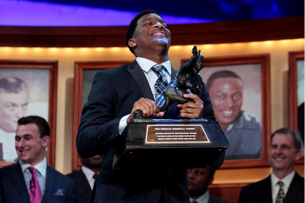 . Jameis Winston, quarterback of the Florida State Seminoles, hoist the trophy after being named the 79th Heisman Memorial Trophy Award winner during the 2013 Heisman Trophy Presentation at the Best Buy Theater on December 14, 2013 in New York City.  (Photo by Kelly Kline/Getty Images for the Heisman Trust)