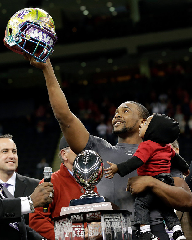 . Louisiana-Lafayette quarterback Terrance Broadway (8) holds his son Terrance and the New Orleans Bowl helmet after defeating East Carolina in the New Orleans Bowl NCAA college football game in New Orleans on Saturday, Dec. 22, 2012. Louisiana-Lafayette defeated East Carolina 43-34. (AP Photo/Skip Martin)