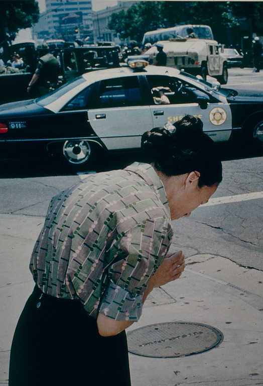 . As Police, Sheriffs and National Guardsmen stood by, a woman stoped at the intersection of 2nd and Spring Streets to offer a prayer for peace. May 2, 1992. (Photo by John McCoy/Los Angeles Daily News).
