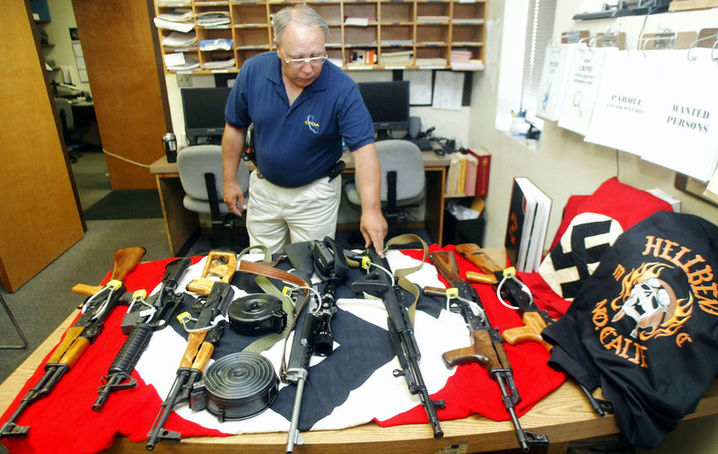 Orland Chief of Police Bob Pasero takes a look at a Russian SKS (3rd from left) among the collection of weapons and Nazi flags at the Orland Police station Thursday which they found after serving a domestic disturbance of an Orland man who supervises trustees at Glenn Jail who was arrested on multiple charges. - Halley photo 7/7/05