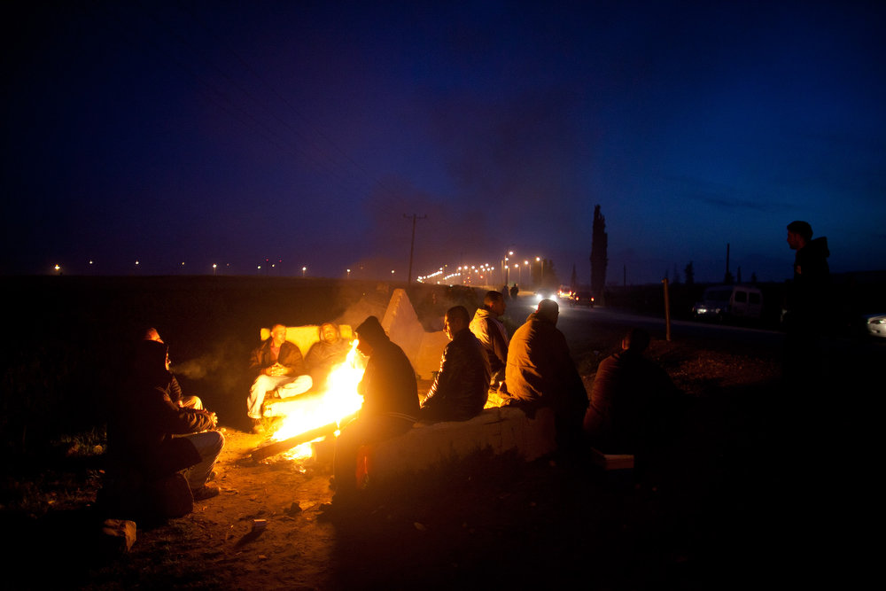 . Palestinians warm up by a fire as they wait for a bus as a new line is made available by Israel to take Palestinian laborers from the Israeli army crossing of Eyal, near the West Bank town of Qalqilya, into Israeli cities on March 4, 2013. The new line service to ferry Palestinian workers from the West Bank to Israel, encouraging them to use it instead of traveling with Israeli settlers on a similar route.  (Photo by Uriel Sinai/Getty Images)