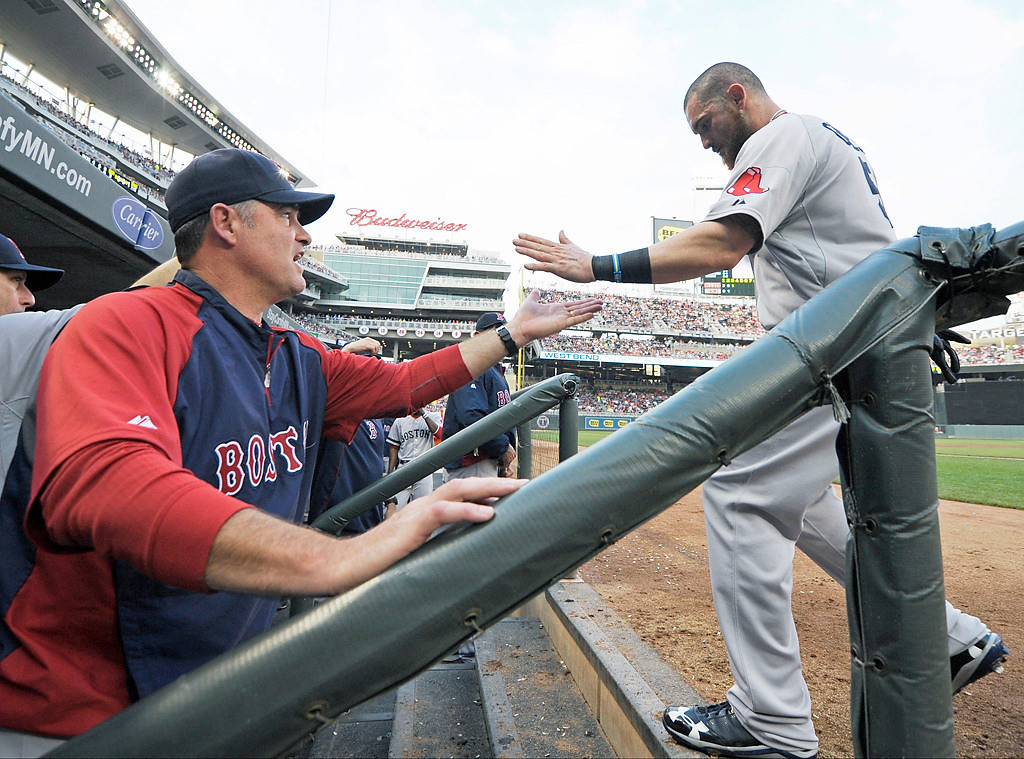 . Boston Red Sox manager John Farrell, left, congratulates Jonny Gomes after he scored in the third inning on a single by David Ortiz. (AP Photo/Jim Mone)