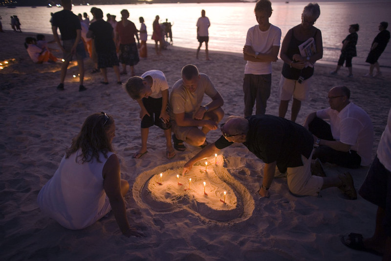 . Western tourist and others light candle during remembrance services at Dolphin Park on Patong Beach in Phuket, Thailand,  Friday, Dec. 26, 2008, on the fourth anniversary of the Asian Tsunami. The victims of the 2004 Indian Ocean tsunami were honored by thousands of mourners who prayed, burned candles and shared meals on beaches from Indonesia to India on Friday, the fourth anniversary of the catastrophe. (AP Photo/David Longstreath)