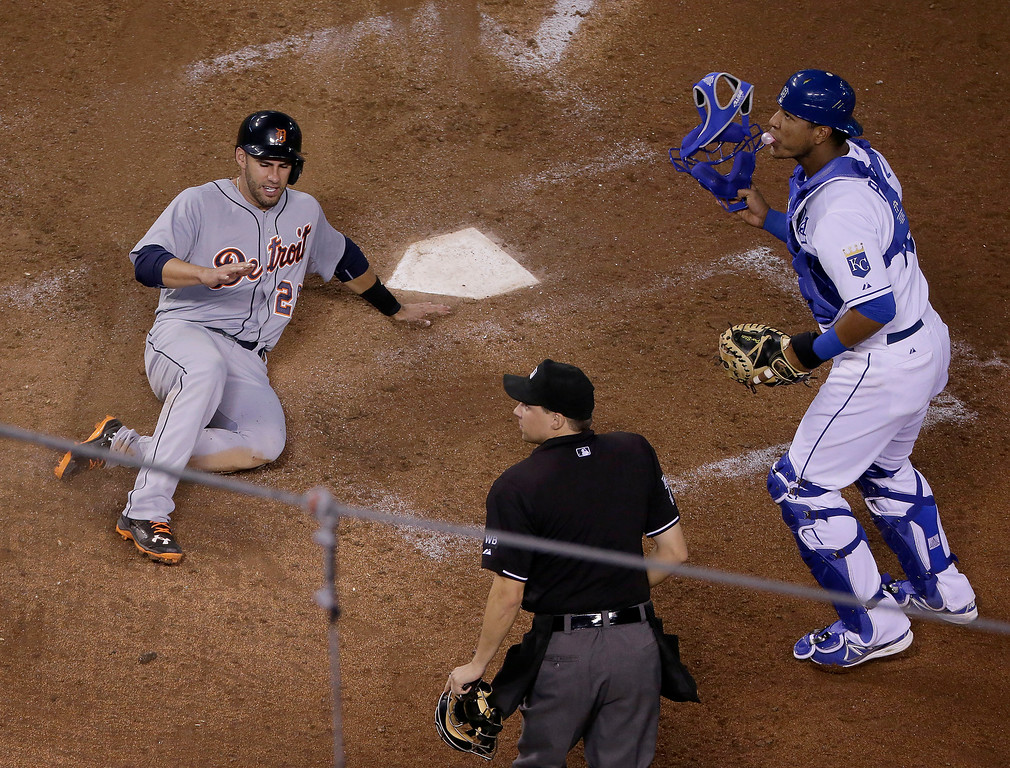 . Detroit Tigers\' J.D. Martinez slides home to score on a single by Torii Hunter as Kansas City Royals catcher Salvador Perez looks for the ball that was overthrown by center fielder Jarrod Dyson during the fifth inning of a baseball game Thursday, July 10, 2014, in Kansas City, Mo. Dyson was given an error on the play. (AP Photo/Charlie Riedel)