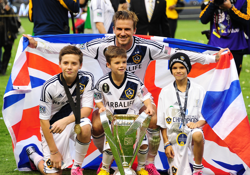 . A picture taken on December 1, 2013 shows David Beckham posing with his sons Brooklyn (L), Cruz (C) and Romeo and the MLS Trophy after the Los Angeles Galaxy beat Houston Dynamo 3-1 in the Major League Soccer (MLS) Cup in Carson,.California. ROBYN BECK/AFP/Getty Images